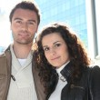 Stock Photo: Couple stood outside modern office block