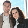 Couple stood outside modern office block - Stock Photo