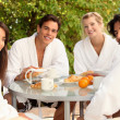 Two young couples sharing breakfast on the terrace - Stockfoto