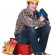 Young tradesman sitting on toolbox holding sander machine — Stock Photo