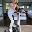 Older woman using an exercise bike — Stock Photo