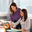 Stock Photo: Young womhelping her colleague