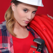Alluring woman holding corrugated tubing and a pipe wrench - Photo