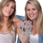 Teenage girls holding @ sign — Stock Photo
