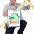 Carpenter kneeling with energy efficiency banner - Stock Photo