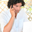 Man sat with laptop and telephone on terrace — Stock Photo #9212080