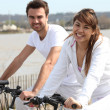 Young couple doing bike near the sea — Stok fotoğraf