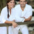 Couple in white leaning on a country fence — Stock Photo #9212579