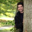 Portrait of a young man next to a tree - Stock Photo