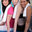 Women sitting on an exercise mat — Stock Photo #9213732