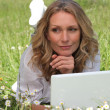 Woman lying on the grass and using her laptop - Photo