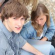 Foto de Stock  : Young students outside with coursework