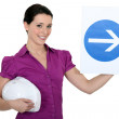 Stock Photo: Woman holding sign of obligation to turn right
