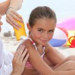 A mother putting sun cream on her daughter's shoulders - Foto Stock