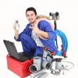 Plumber with laptop, cellphone and materials — Stock Photo