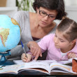 Mother teaching daughter geography — Stock Photo