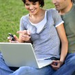 Couple sat in the park with laptop — Stock Photo #9215260