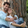 Couple sitting against a tree — Stock Photo