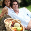 Stock Photo: Couple posing with fruit basket