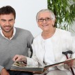 Elderly person looking at photos with son — Stock Photo #9216582