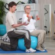 Stock Photo: Womworking out with help of her personal trainer