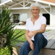 Elderly lady sat on decking — Stock Photo #9217201