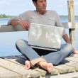 Man on laptop by a lake — Stock Photo #9217875