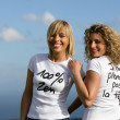 Women wearing slogan t-shirts against a blue sky - Stock Photo