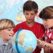 Three kids learning geography. — Stock Photo