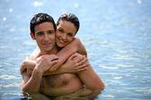 Giovane coppia abbracciarsi in acqua — Foto Stock