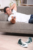 Man relaxing on sofa watching television — Stock Photo