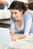 Young woman using a laptop on the floor at home — Stock Photo