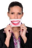 Woman holding a photo of lips to her mouth — Stock Photo