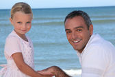 Father and daughter holding hands on the beach — Stock Photo