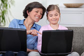 A mother and her daughter on their laptops. — Stock Photo