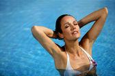 Brunette stood in pool wearing white bikini — 图库照片