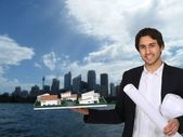 Architect holding model with urban landscape in background — Stock Photo