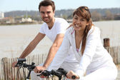 Young couple doing bike near the sea — Stock Photo