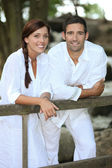 Couple in white leaning on a country fence — Stock Photo