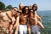 Deniz kenarında eğleniyor genç arkadaş grubu — Stok fotoğraf