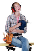 Woman sat on work-bench holding saw — Stock Photo