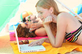 Young woman using a laptop computer on the beach — Stock Photo
