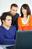 Three workers gathered around laptop — Stock Photo