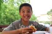 Child eating breakfast outside — Stock Photo