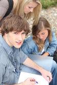 Jeunes étudiants à l'extérieur avec le coursework — Photo
