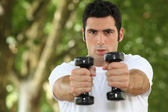 Young man doing fitness in a park — Stock Photo