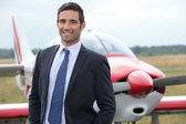 Smiling businessman standing in front of a light aircraft — Stock Photo