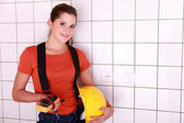 Handywoman posing with an ammeter and a helmet — Stock Photo