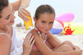 A mother putting sun cream on her daughter's shoulders — Stock Photo