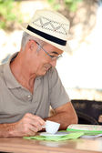 Retired man looking at a map while drinking coffee — Stock Photo